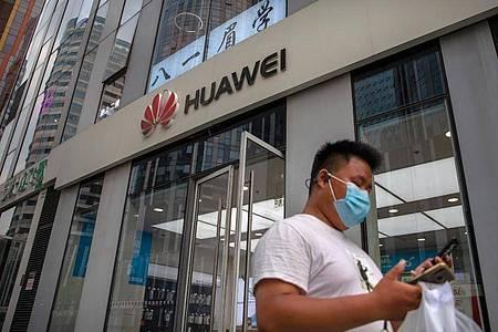 Ein Mann mit Gesichtsmaske schaut auf sein Smartphone, als er an einem Huawei-Laden in Peking vorbeigeht. Foto: Mark Schiefelbein/AP/dpa