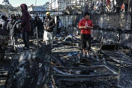 Migranten stehen auf den abgebrannten Überresten des Gemeinschaftszentrums. Foto: Panagiotis Balaskas/AP/dpa