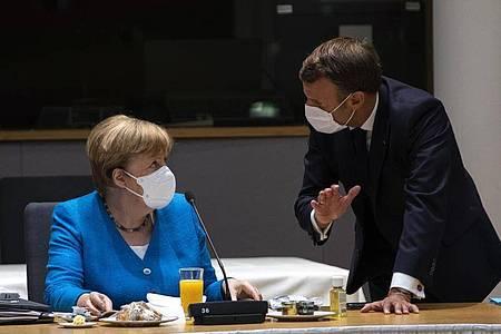 Bundeskanzlerin Angela Merkel spricht mit dem französischen Präsidenten Emmanuel Macron am zweiten Tag des EU-Gipfels. Foto: Francisco Seco/AP Pool/dpa