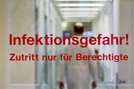 """""""Infektionsgefahr! Zutritt nur für Berechtigte"""" steht an der Tür am Institut für Medizinische Mikrobiologie, Virologie und Hygiene in Rostock. Foto: Bernd Wüstneck/dpa-Zentralbild/dpa"""