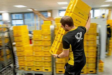 Der Auszubildende lernt, worauf es bei der Arbeit als Fachkraft für Kurier-, Express- und Postdienstleistungen ankommt. Foto: Klaus-Dietmar Gabbert/dpa-tmn