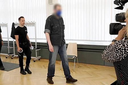 Justizmitarbeiter führen den 39-Jährigen in den Saal des Rostocker Landgerichts. Foto: Bernd Wüstneck/dpa-Zentralbild/dpa