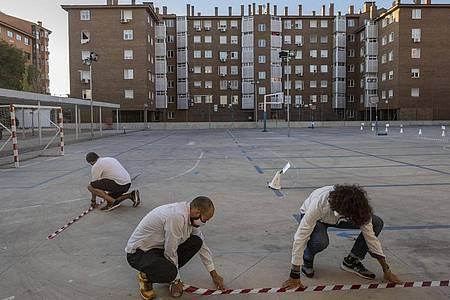 Lehrer machen mit Klebeband Markierungen auf dem Boden des Schulhofs der internationalen J.H.Newman-Schule in Madrid, um den Sicherheitsabstand zwischen den Schülern zu gewährleisten. Foto: Bernat Armangue/AP/dpa