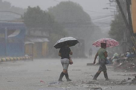 Zwei Frauen überqueren bei starkem Regen eine Straße in La Lima in Honduras. Foto: Delmer Martinez/AP/dpa