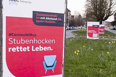 Eine Plakat-Kampagne des Stadtmarketings in Kiel fordert die Bürger auf, zu Hause zu bleiben. Foto: Frank Molter/dpa