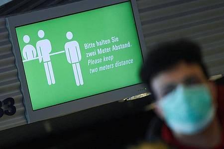 """Rückkehrer nach Deutschland werden wohl bald ins Quarantäne müssen. Auf dem Monitor am Frankfurter Flughafen steht:""""Bitte halten Sie zwei Meter Abstand!"""" . Foto: Arne Dedert/dpa"""