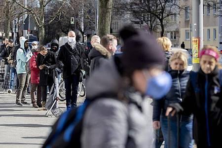 Zahlreiche Menschen stehen in Berlin vor einem Supermarkt Schlange. Foto: Christoph Soeder/dpa