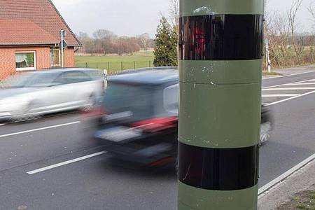 Autos fahren an einem Blitzgerät zur Geschwindigkeitskontrolle vorbei. Wegen eines Formfehlers in der Straßenverkehrsverordnung sind die neuen Regeln von den Bundesländern vorerst außer Vollzug gesetzt worden. Foto: picture alliance / Julian Stratenschulte/dpa