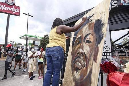 Eine Künstlerin malt ein Bild des Opfers Rayshard Brooks. Foto: Steve Schaefer/Atlanta Journal-Constitution/AP/dpa