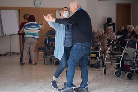 Altenpfleger beim Tanz mit Bewohnern des Marienstift während eines Auftritts von Schlagersänger Freddy Caruso im Garten des Altenheimes. Foto: Julian Stratenschulte/dpa