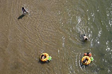 Kinder baden bei einer Temperatur von weit über 30 Grad an einer flachen Stelle des Rheins in Köln. Foto: Henning Kaiser/dpa