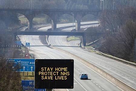 Eine digitale Anzeigentafel an einer Autobahn appelliert an die Fahrer, möglichst zu Hause zu bleiben. Foto: Andrew Milligan/PA Wire/dpa