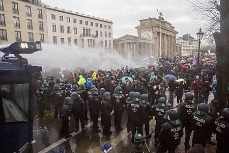 Die Polizei setzt Wasserwerfer gegen die Demonstranten ein. Foto: Christoph Soeder/dpa