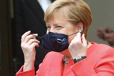 Bundeskanzlerin Angela Merkel (CDU) nimmt im Bundesrat ihre Mund- und Nasenschutzmaske ab, bevor sie eine Rede zu Zielen der EU-Ratspräsidentschaft hält. Foto: Wolfgang Kumm/dpa