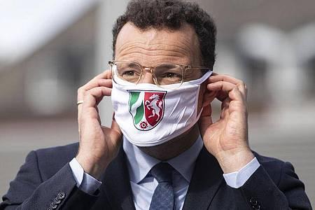 Bundesgesundheitsminister Spahn setzt sich nach einem Klinik-Besuch in NRWeinen Mund-Nasen-Schutz auf. Foto: Marius Becker/dpa/Archiv