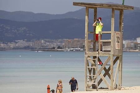 Ein Rettungsschwimmer beobachtet den Strand von El Arenal auf Mallorca. Foto: Clara Margais/dpa