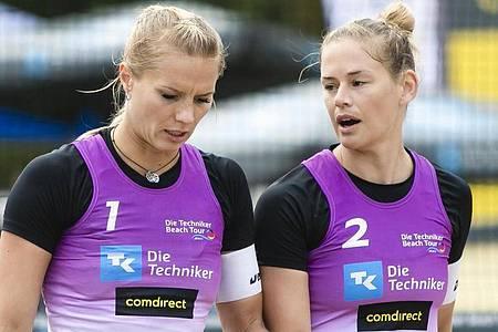 Kim Behrens (l) und Cinja Tillmann unterhalten sich bei den Deutschen Beachvolleyball-Meisterschaften. Foto: Frank Molter/dpa