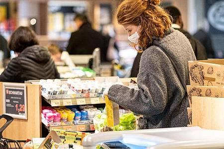 Sicher ist sicher:Mit einer Schutzmaske kauft eine Frau in einem Supermarkt ein. Foto: Peter Steffen/dpa