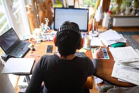 Eine Frau arbeitet mit Hörschutz im Homeoffice. «Alle Beschäftigten bekommen das Recht, mit ihrem Chef über mobiles Arbeiten zu verhandeln», so Arbeitsminister Heil. Foto: Sebastian Gollnow/dpa