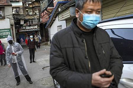 Menschen halten Abstand, während sie in Wuhan für Schweinefleisch anstehen. Foto: Uncredited/CHINATOPIX/dpa