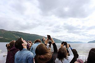 Touristen auf einem Schiff nutzen ihre Handys