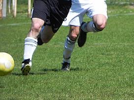 Zwei Fußballer laufen dem Ball hinterher