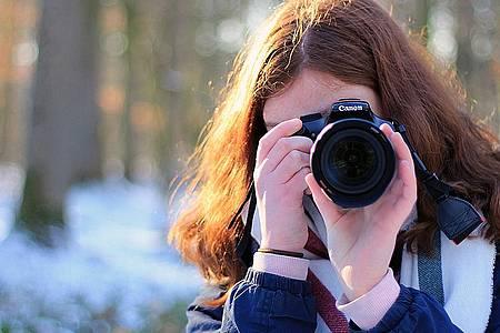 Frau mit Kamera vor dem Gesicht