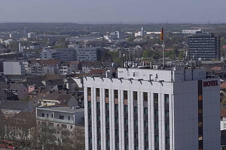 Auf der Kante eines Hotels sitzt eine Frau und lässt die Beine baumeln, im Hintergrund sieht man die Dächer von Paderborn