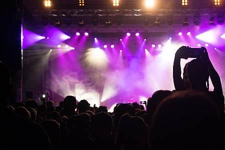 Bühne mit Menschen davor und lila Licht