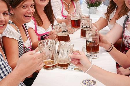 Frauen stoßen mit einer Maß Bier an