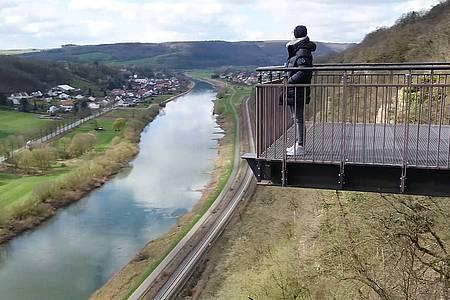 """Eine Frau steht auf der Aussichtsplattform """"Weser-SkyWalk"""" unter ihr erkennt man die Weser"""