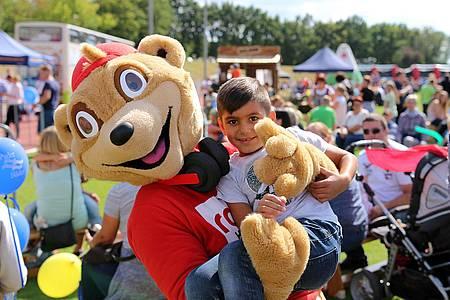 Radio Hochstift Maskottchen Eddy trägt ein Kind auf dem Arm
