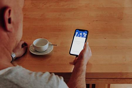 Mann hält Smartphone mit Facebook-App